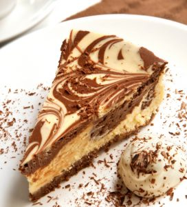 Chocolate marble cheesecake with cream and shaved chocolate, and a cup of coffee.